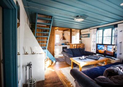 Öppen planlösning i stora stugan med öppen spis, tv-rum och kök