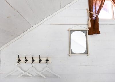 Lilla fönstret mot skogen uppe i sovloftet i lilla stugan och spegel med klädhängare