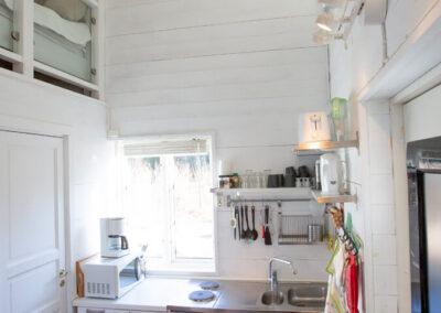 Lilla stugan har en köksdel med kylskåp, spisplattor och mikrovågsugn och tv-rumsdel
