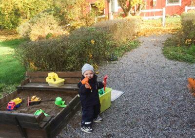 Lek i sandlådan i vår familjevänliga trädgård.