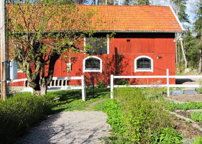 The horse stable on the other side of the garden.