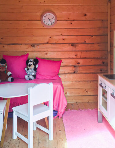 The child friendly garden with apple trees and playhouse.